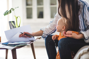 Working mother examining documents with daughter at home