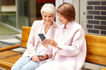 technology, old age and people concept - happy senior women or friends with smartphones sitting on bench in city