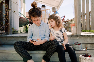 Sibling using smartphone while sitting on steps