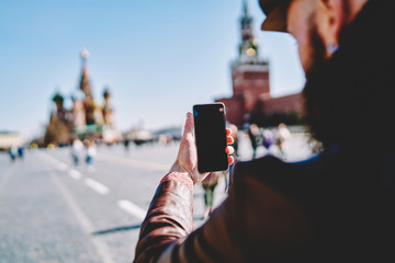Back view of male traveller taking images on smartphone gadget with blank screen for your internet content or website during exploring Red Square in Moscow, concept of technology and sightseeing