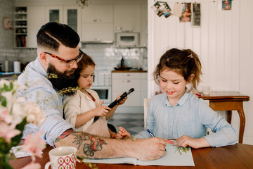 Father assisting girl in homework while sitting with daughter at dining table