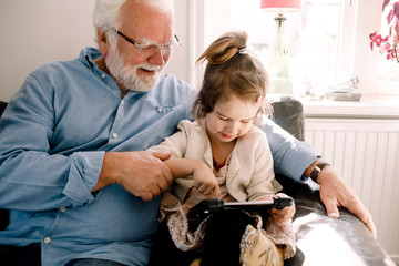 Girl using digital tablet while sitting with grandfather on sofa at home