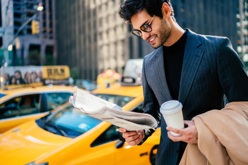 Smiling successful entrepreneur in elegant suit satisfied with article in daily press standing on avenue with blank coffee cup, happy businessman reading newspaper waiting for yellow cab on Manhattan.