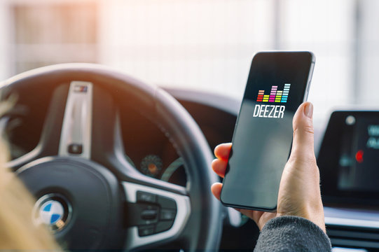 AACHEN, GERMANY AUGUST 2019: Woman holding a Apple iPhone opening Deezer Music streaming app in a car. Streaming music via the Internet