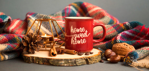 Autumn coffee cup with candle, spices and blanket decorations on wooden board, cozy fall deco concept, home lifestyle warm coffee cup in autumn season