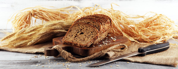 Foto op Aluminium Brood freshly baked bread on wooden board. cutted organic bread