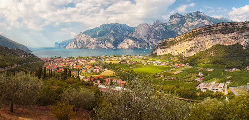 Lake coast with mountains and cliffs around, in the foreground village, green meadows, fields and olive trees, blue sky with white clouds. Lago di garda near the Alps (near Trombole, Riva del garda). Fototapete