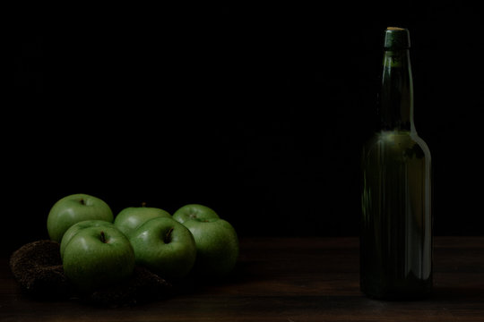 Green apples, cider on wood with black background and space for writing.