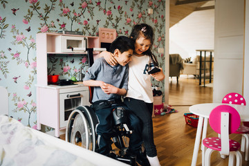 Girl and disabled brother looking at smartphone, laughing