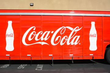 Closeup of a Coca-Cola Delivery truck outside a market.