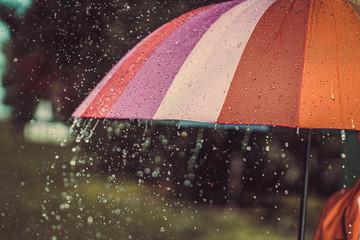 Bright colored rainbow umbrella in the rain autumn weather Fotobehang