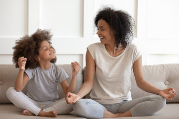 Recess Fitting Zen Excited african american woman practicing yoga with little daughter.