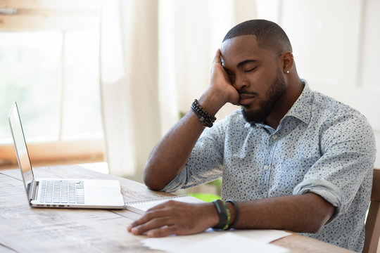 Tired african american man sleeping in front of computer.
