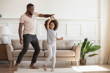 Excited loving african american smiling father twisting cute little daughter.
