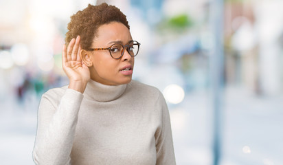 Young beautiful african american woman wearing glasses over isolated background smiling with hand over ear listening an hearing to rumor or gossip. Deafness concept.