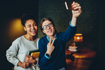 Joyful multiracial male and female friends posing for selfie on smartphone camera during free time indoors, young colleagues enjoying leisure together making funny faces for taking image on cellphone.