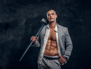 Young attractive hot man in suit and opened white shirt is holding long hammer in hand.