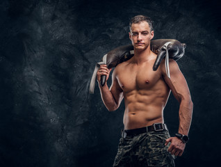 Muscular attractive hot man is holding weight bag while posing for photographer.