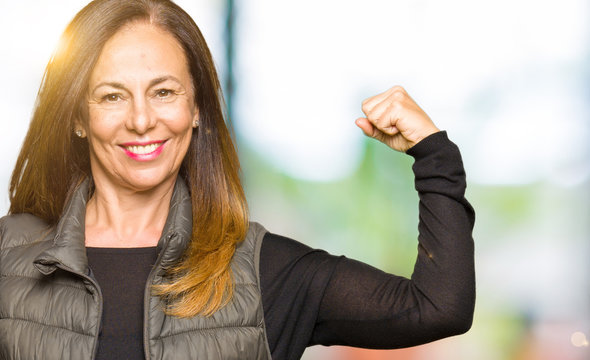 Beautiful middle age woman wearing winter vest Strong person showing arm muscle, confident and proud of power