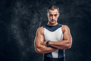 Portrait of muscular handsome man in wetsuit crossed his hands over dark background.