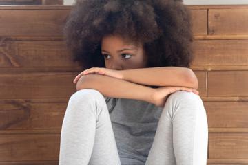 Offended little african american girl sitting on floor. Fototapete