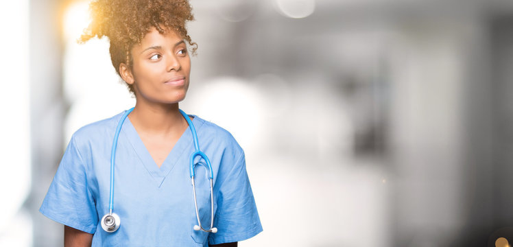 Young african american doctor woman over isolated background smiling looking side and staring away thinking.