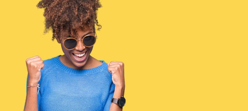Beautiful young african american woman wearing sunglasses over isolated background very happy and excited doing winner gesture with arms raised, smiling and screaming for success. Celebration concept.