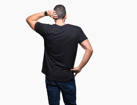 Young handsome man over isolated background Backwards thinking about doubt with hand on head