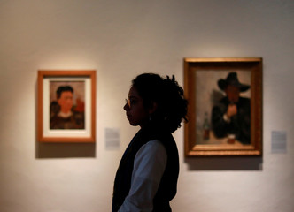 A woman looks on during the exhibition of paintings of Mexican muralist Diego Rivera and Mexican artist Frida Kahlo, in Mexico City