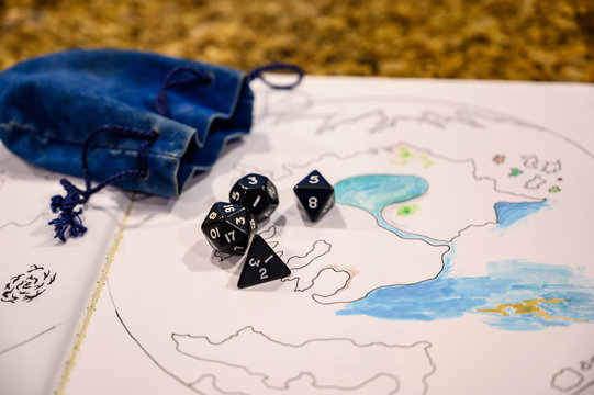 Role playing dice scattered on top of drawing of a map
