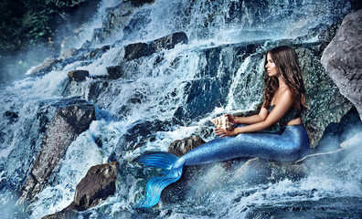 Side view picture of a mermaid sitting in the waterfall
