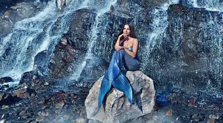 Wide picture of a dreaming mermaid against waterfall background