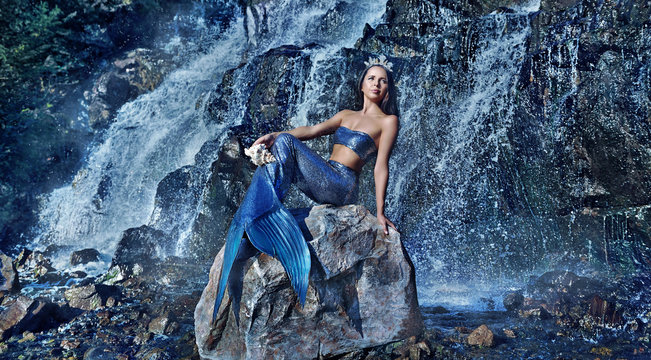 Wide picture with the mermaid against waterfall