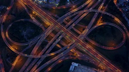 Fotobehang - 4K. Aerial view of road interchange or highway intersection with busy urban traffic speeding on the road at night. Junction network of transportation taken by drone.