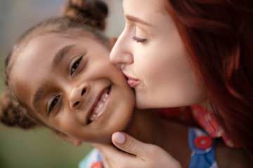 Adopted girl smiling broadly while mother kissing her