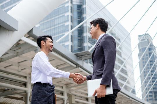 Handsome businessman partnership with handshake agreement of asean economics community
