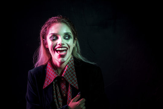 Woman dressed as joker laughing hysterically