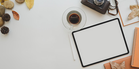 Blank screen tablet, vintage camera, coffee cup and office supplies on white table with copy space