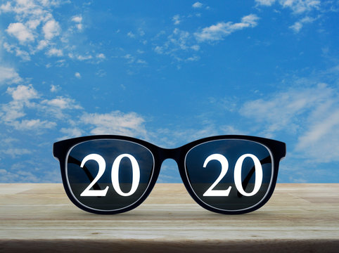 2020 white text with black eye glasses on wooden table over blue sky with white clouds, Business vision happy new year 2019 concept