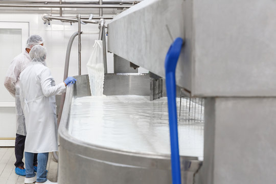 Two technologists standing at  the stainless mixing tank with milk before the fermentation process at the cheese manufacturing.