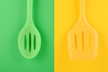 bright kitchen utensils on yellow and green background, creative idea