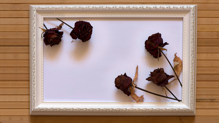 White frame with five dried red roses and empty white canvas on natural bamboo wall. Horizontal picture 16:9 with useful design for input your inside text, image etc.
