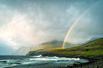 Dramatic landscape of Faroe Island with stormy clouds and rainbow.