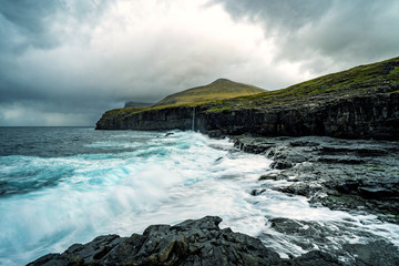 Dramatic landscape of Faroe Island with one of many waterfalls.