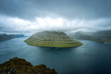 Spectacular views of the scenic fjords on the Faroe Islands near the village Klaksvik with cloud-covered mountains.