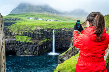 Young female travelers is taking photo of Mulafossur Waterfall with the village Gasadalur in background, Faroe Islands.