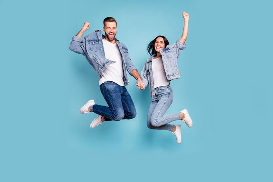 Photo of rejoicing overjoyed nice charming couple wearing jeans denim jackets enjoying their free time in summer while isolated with blue background