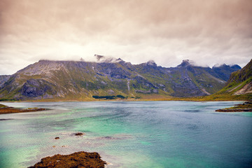 Fototapete - Fjord at sunset. Rocky beach in the evening. Beautiful nature of Norway. Picturesque Scandinavian landscape