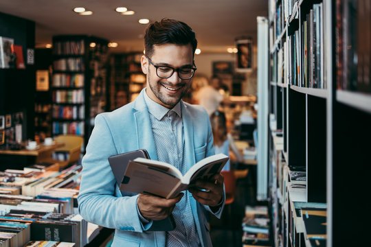 Middle age man choosing and reading books in modern bookstore.
