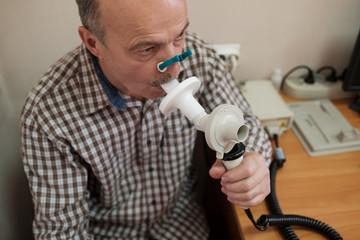 Senior hispanic man man testing breathing function by spirometry. Diagnosis of respiratory function...